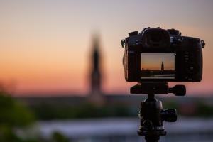 detalle de camara negra DSLR con focus en la puesta del sol